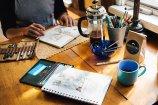 Notebooks, pens, beverages... bliss for the writer. Image via Pixabay.