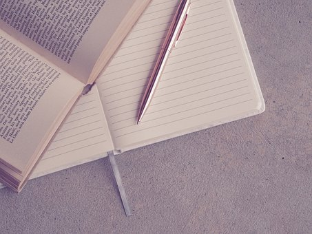 Research material, notebook and pen to hand. Image via Pixabay