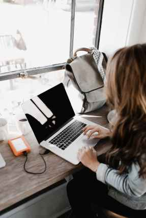 close up photography of woman sitting beside table while using macbook